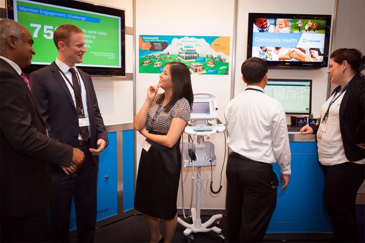 people talking at the Cerner stand